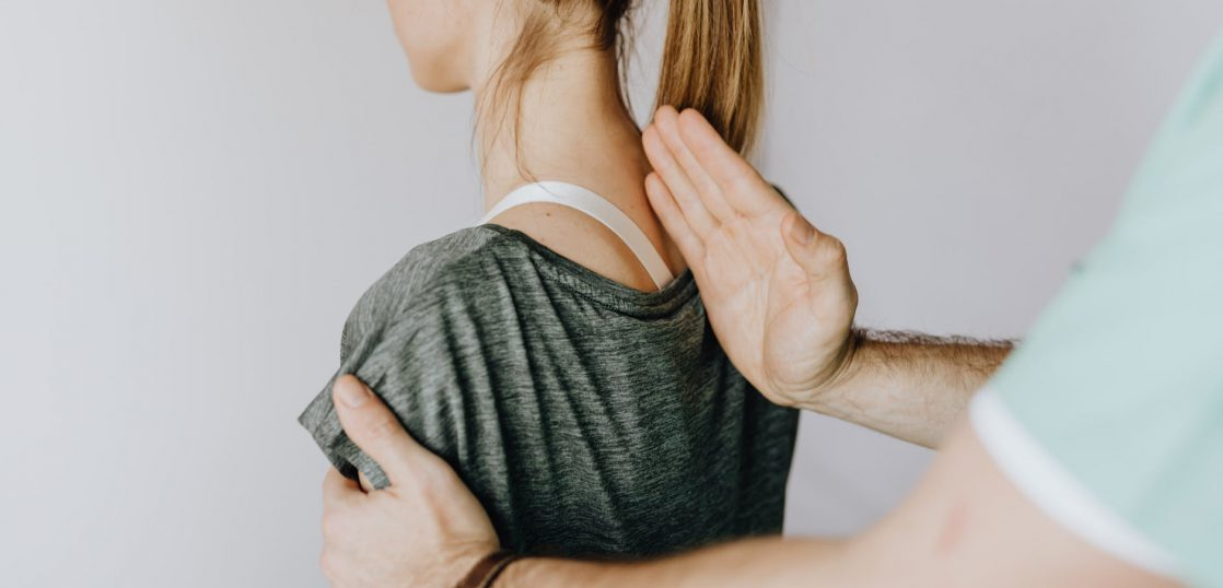 crop anonymous chiropractor examining spine of fit lady in hospital